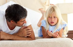 Little girl talking seriously with her father lying on bed