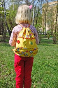 Small girl wearing a backpack full of joy