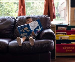 Preschooler, sitting in a huge leather chair, and totally engrossed in a fun book.