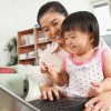 Asian mom and child on laptop laughing