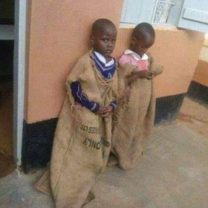This image from Facebook shows two children forced to wear sacks for speaking Luganda in school.