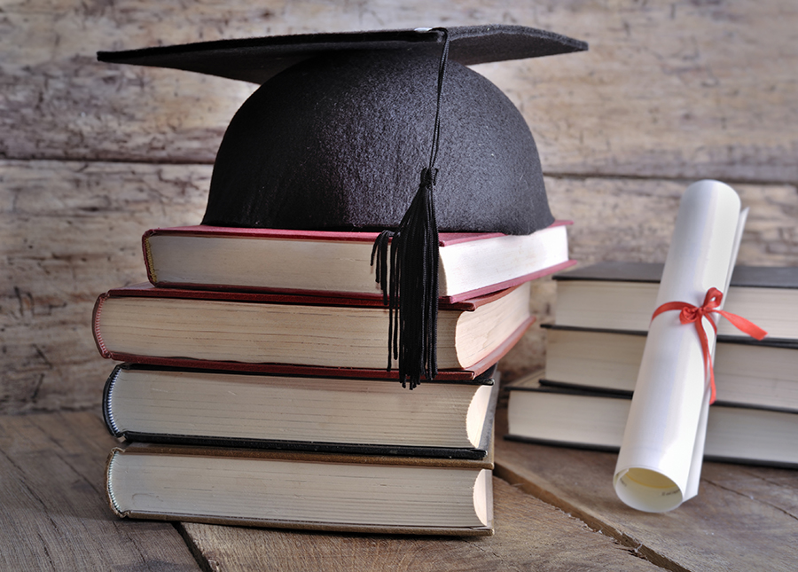 Diploma rolled up in a red ribbon and a black mortarboard hat on pile of books